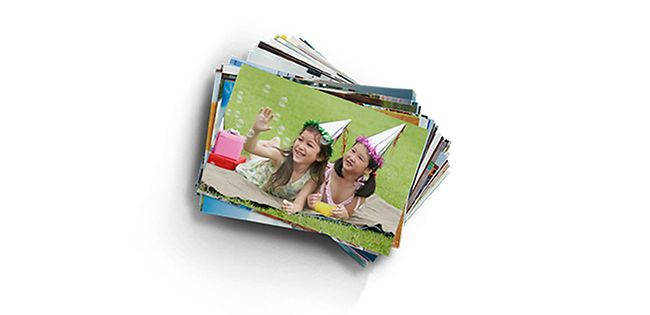 Two girls smiling in photo on top of print stack