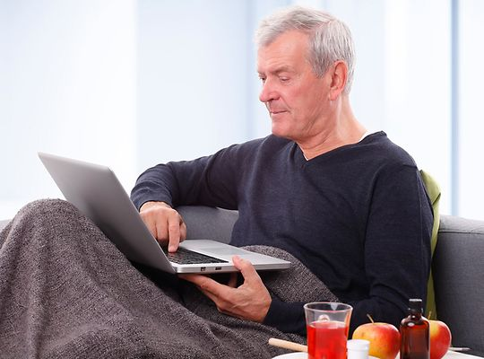 Man under blanket on laptop