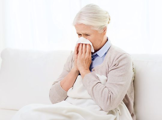 Elderly woman under blanket blowing nose