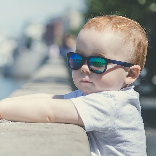 Child in sunglasses looking at river