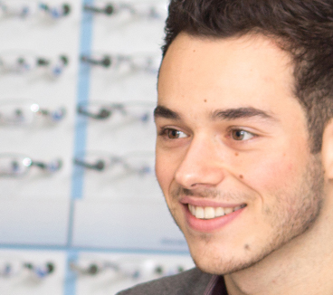 Man smiling with opticians display of glasses visible in the background
