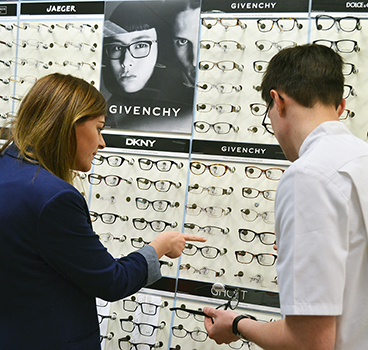 Woman trying on glasses to buy from a selection
