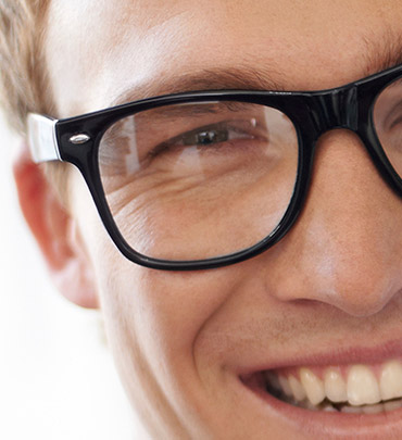 Smiling young man in dark-rimmed glasses