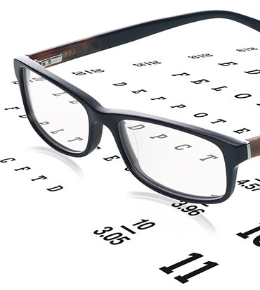 A pair of glasses sat on eye check letters and numbers chart