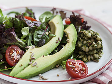 A plate of salad with green leaves, avocado and tomatoes