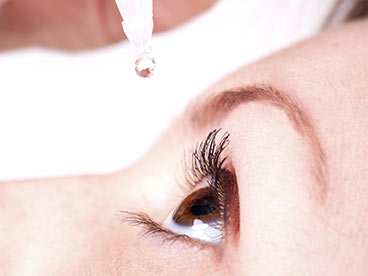 A woman putting eye drops into her eye